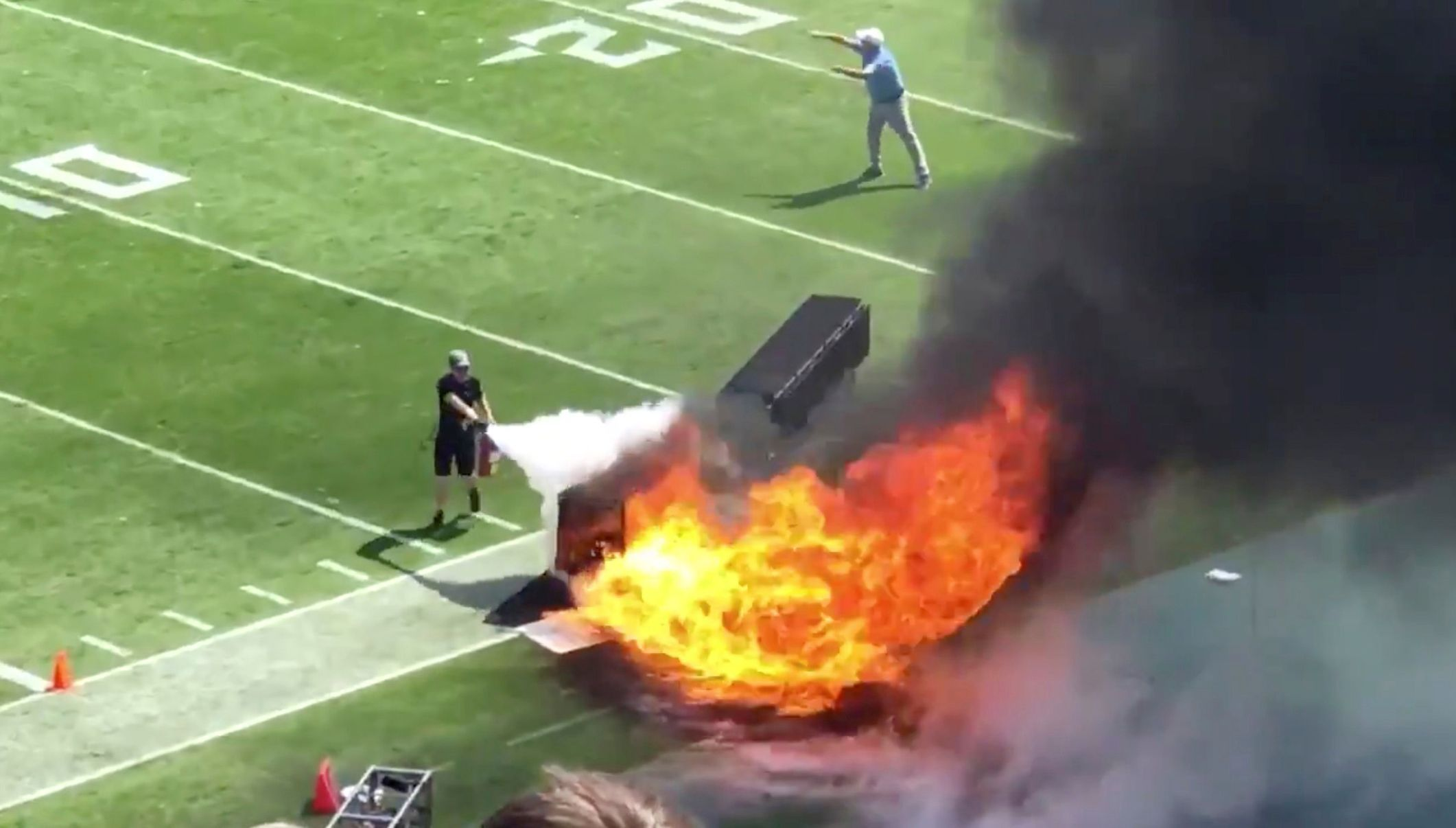 People try and extinguish fire from burning equipment used during pregame, du
