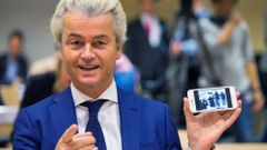 Dutch far-right Party for Freedom leader Geert Wilders shows the picture of the photographers he took with his cell phone prior to his trial in the courtroom in the courthouse in Schiphol
