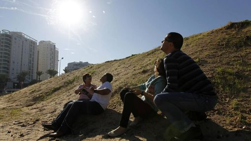Israeli people look up at the sky with smoke trails from an Iron Dome interceptor rocket and try to take cover as a siren sounds warning of incoming rockets in Ashdod November 15, 2012. Hamas fired dozens of rockets into southern Israel on Thursday, killing three people, and Israel launched numerous air strikes across the Gaza Strip, threatening a wider offensive to halt repeated Palestinian salvoes. REUTERS/Amir Cohen (ISRAEL - Tags: CIVIL UNREST) Published: Lis. 15, 2012, 9:42 dop.