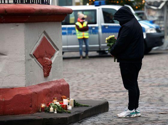 Lidé nosí svíčky k místu v Trevíru, kde řidič najel do skupiny chodců.