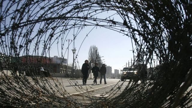 "Women are seen behind barbed wire, as they cross a bridge from the Albanian side to the Serb side in the ethnically divided Kosovo town of Mitrovica February 14, 2008. Serbia will not allow itself to be humiliated by a ""puppet state"" on its territory, Prime Minister Vojislav Kostunica said on Thursday as Serbia prepared to annul Kosovo's proclamation of independence in advance.REUTERS/Marko Djurica (SERBIA)"