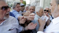 Řecko Pensioners are given priority tickets as they wait to receive part of their pensions at a National Bank branch in Athens