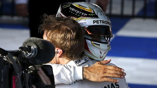 Mercedes F1 driver Nico Rosberg (R) is hugged by team mate Lewis Hamilton after winning the Australian Formula One Grand Prix in Melbourne