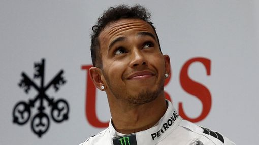 First-placed Mercedes Formula One driver Lewis Hamilton of Britain looks up as he stands on the winners' podium during the Chinese F1 Grand Prix at the Shanghai Internati