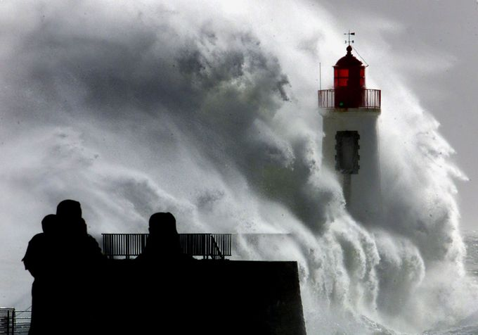 Two silhouetted people watch a powerfull wave as it hits a lighthouse at the entrance of Les Sables D'Olonne harbour.