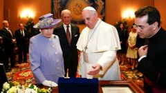 Pope Francis presents gift to Britain's Queen Elizabeth as Prince Philip looks on during a meeting at the Vatican