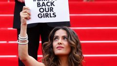 "Actress and producer Salma Hayek holds a placard which reads ""Bring back our girls"" as she poses on the red carpet at the 67th Cannes Film Festival in Cannes"