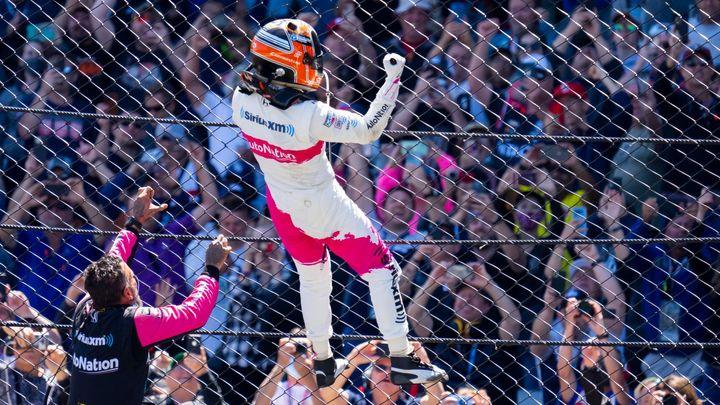 """Bláznivá oslava Indy 500: Brazilský """"Spiderman"""" vylezl na plot a pak se polil mlékem; Zdroj foto: Reuters"""