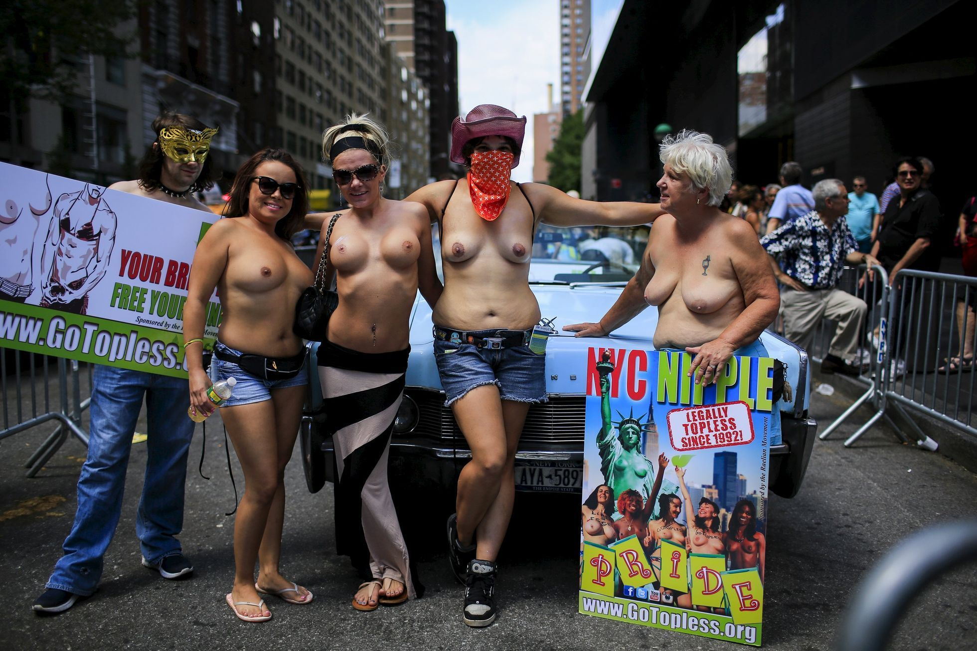 Women pose for a picture before starting a topless march in New York